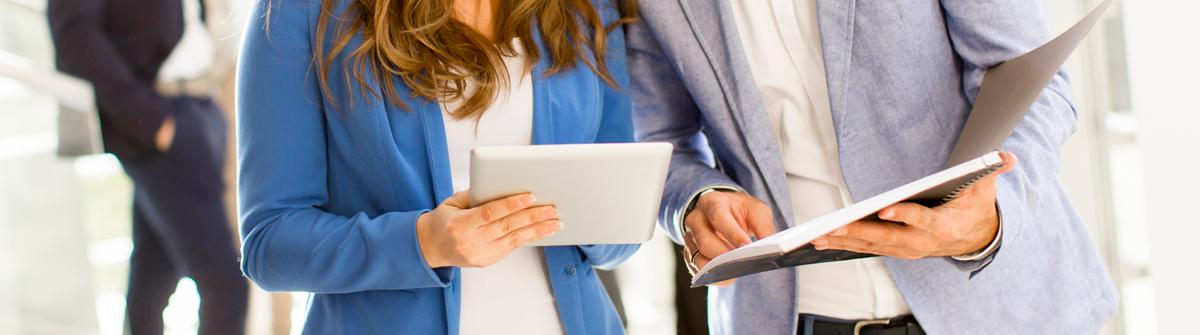 Imagen de una mujer junto a un hombre revisando información en una tablet.