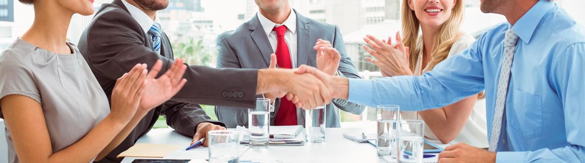 Imagen de un grupo de personas en una reunión cerrando un trato.