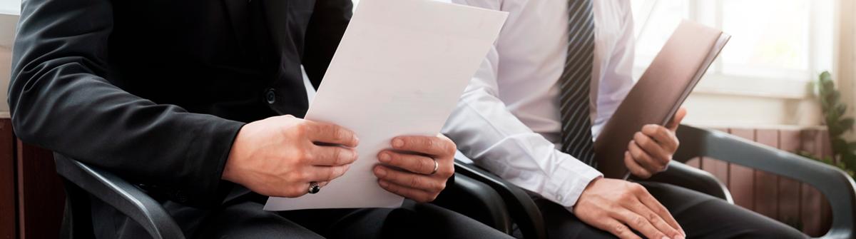 Imagen de dos hombres sentados en una sala de espera con documentos en las manos.