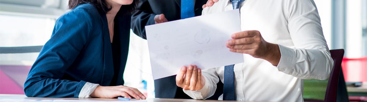 Imagen de tres ejecutivos visualizando un reporte